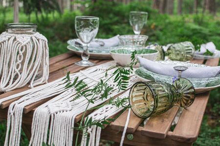 Wedding reception table with macrame tablecloth, decoration on a rustic wooden table Фото со стока - 127115203