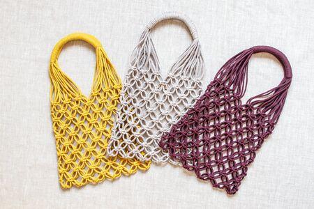 Handmade macrame shopping bags on the light background