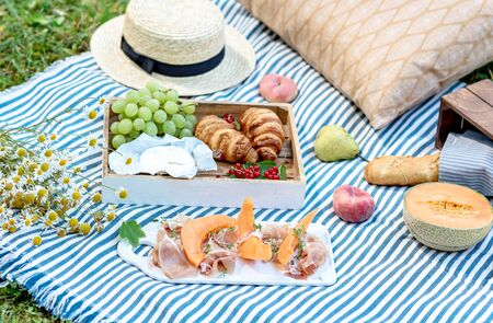 Summer picnic on the grass, jamon with melon, grape, bakery, fruits. Rest time, healthy food concept