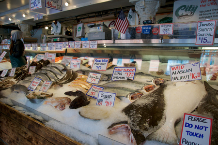 SEATTLE, WASHINGTON, USA - JAN 24th, 2017: Customers at Pike Place Fish Company wait to order fish at the famous seafood market. This market, opened in 1930, is known for their open air fish market style.