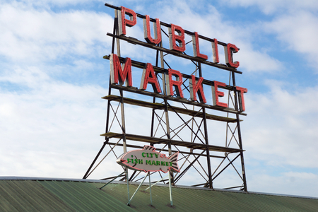 pike place: SEATTLE, WASHINGTON, USA - JAN 24th, 2017: Neon public market sign against cloudy sky, Pikes Place Market in downtown is a famous sight.