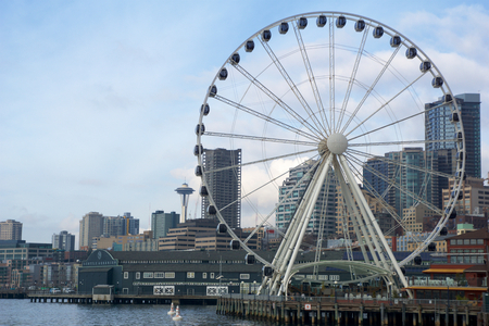puget: SEATTLE, WASHINGTON, USA - JAN 25th, 2017: A view on Seattle downtown from the waters of Puget Sound. Piers, skyscrapers, Space Needle and Ferris wheel in Seattle city before sunset Editorial