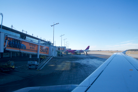 NUREMBERG, GERMANY - JAN 20th, 2017: Aircraft window view of the Nuremberg airport apron airport terminal with airplanes parked to gates airport trucks air traffic control tower on background