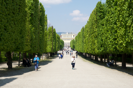 VIENNA, AUSTRIA - APR 30th, 2017: Public park in Schonbrunn Palace Schonbrunn Palace. Its a former imperial 1441-room Rococo summer residence of Sissi Empress Elisabeth of Austria in modern Wien. Tourist walking in the park