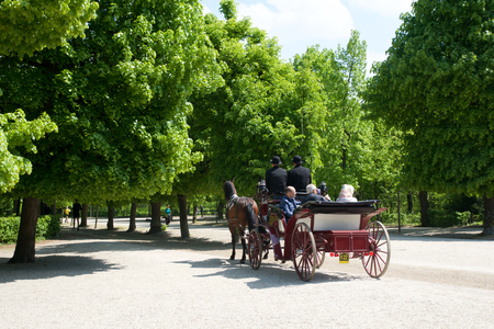 VIENNA, AUSTRIA - APR 30th, 2017: Public park in Schonbrunn Palace Schonbrunn Palace. Its a former imperial 1441-room Rococo summer residence of Sissi Empress Elisabeth of Austria in modern Wien. Carraige with tourists riding throug he park