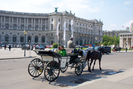 VIENNA, AUSTRIA - APR 29th, 2017: Famous horse-driven carriage at Hofburg Palace in Vienna. It was the Habsburgs principal winter residence, currently serves as the residence of the President of Austria