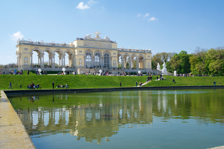 schoenbrunn: VIENNA, AUSTRIA - APR 29th, 2017: The Gloriette houses a cafe and an observation deck which provides panoramic views of the Schonbrunn Palace and gardens, clear sky with some clouds and reflection in water