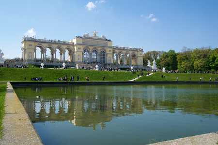 schloss schonbrunn: VIENNA, AUSTRIA - APR 29th, 2017: The Gloriette houses a cafe and an observation deck which provides panoramic views of the Schonbrunn Palace and gardens, clear sky with some clouds and reflection in water
