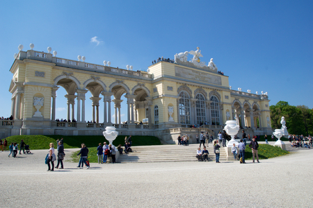 schloss schonbrunn: VIENNA, AUSTRIA - APR 29th, 2017: The Gloriette houses a cafe and an observation deck which provides panoramic views of the Schonbrunn Palace and gardens, clear sky with some clouds in the background