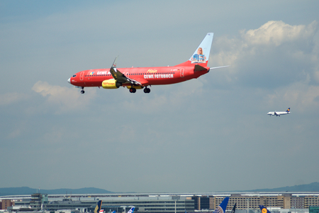 FRANKFURT, GERMANY - JUL 09th, 2017: TUIfly AIRLINES Boeing 737-800 with red advertisement lands with another plane in the background at Frankfurt airport, Boeing 737 Next Gen, MSN 30883, Registration D-AHFZ, TUIfly-a German leisure airline owned by the t Sajtókép