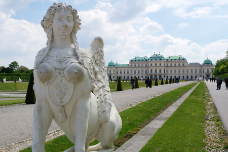 esfinge: VIENNA, AUSTRIA - APR 30th, 2017: Upper Belvedere Palace with a close-up of a statue of a horse at the entrance on a sunny day with blue sky and clouds in summer and tourists walking Editorial