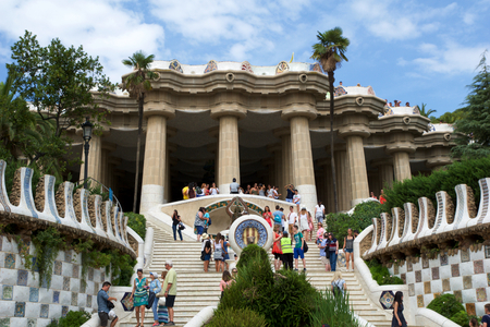 BARCELONA, SPAIN - AUG 30th, 2017: Entrance at the Park Guell designed by Antoni Gaudi with tourists at the stairs, Catalonia