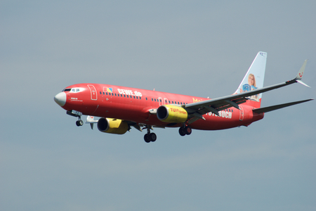 FRANKFURT, GERMANY - JUL 09th, 2017: TUIfly AIRLINES Boeing 737-800 with red advertisement lands at Frankfurt airport, Boeing 737 Next Gen, MSN 30883, Registration D-AHFZ, TUIfly-a German leisure airline owned by the travel and tourism company TUI Group