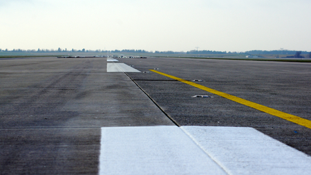 BERLIN, GERMANY - JAN 17th, 2015: Runway, airstrip on blue sky with clouds background at the Berlin Brandenburg Airport BER Редакционное