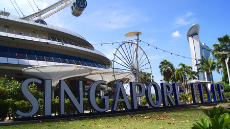 SINGAPORE - APR 2nd 2015: Day view of the Singapore Flyer and the sign. At a height of 165m, Singapore Flyer is the worlds largest giant observation ferries wheel
