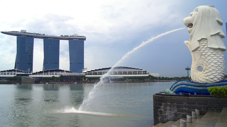 SINGAPORE - APR 2nd 2015: The Merlion fountain and Singapore skyline. Merlion is a mythical creature with the head of a lion and the body of a fish. Is seen as a symbol of the city 新聞圖片