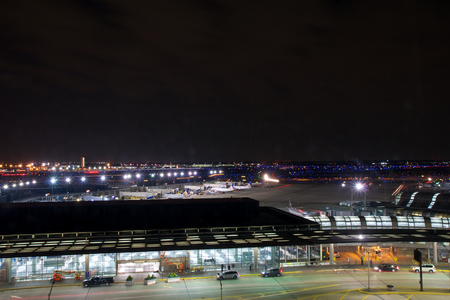 CHICAGO, ILLINOIS, UNITED STATES - MAY 11th, 2018: Outside of Chicago OHare International Airport at night with some cars and airplanes at the terminal Editorial