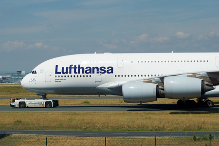 FRANKFURT, GERMANY - JUN 09th, 2017: Airbus A380 of Lufthansa with registration D-AIMH moves on taxiway by tow truck before departure from FRA airport
