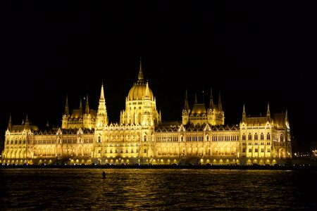 BUDAPEST, HUNGARY - MAR 07th, 2019: The Hungarian Parliament Building is the seat of the National Assembly of Hungary at the Danube river during night, one of Europes oldest legislative buildings