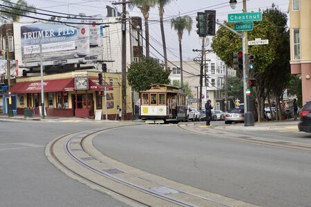 SAN FRANCISCO, CALIFORNIA, UNITED STATES - NOV 25th, 2018: Passengers enjoy a ride in a cable car and crossing street Columbus and Chestnut. It is the oldest mechanical public transport which is in service since 1873