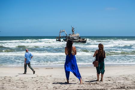 Two Women, a Man and a Shipwreck Just off a Beach near Swakopmund along Namibias Shipwreck Coast
