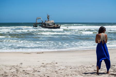 A Woman and a Shipwreck Just off a Beach near Swakopmund along Namibias Shipwreck Coast Stock Photo