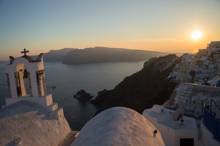 Whitewashed Houses and Church on Cliffs with Sea View and Sunset in Oia, Santorini, Cyclades, Greece Stock Photo