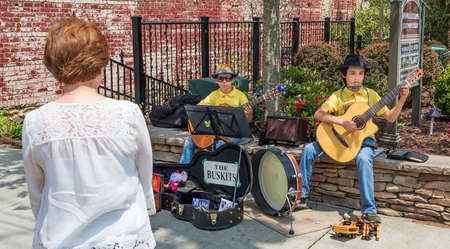 BLOWING ROCK, NC, USA-11 MAY 18: Two young boys busking with guitars on main street in Blowing Rock,  being watch by a red-haired woman bystander. Editorial