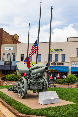 HICKORY, NC, USA-27 MAY 18: On Memorial day weekend,  a WW1 German  cannon captured by American forces in 1918 sets in the town square , with the American flag behind it at half-mast.