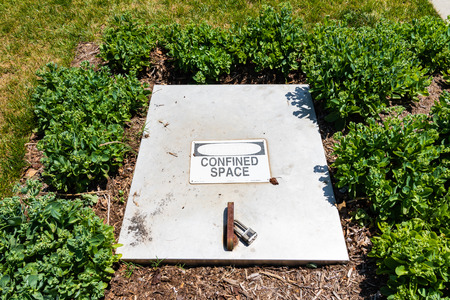 Locked rectangular manhole cover with sign saying confined space. Sajtókép