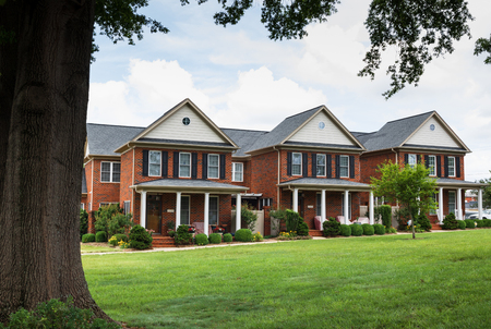 HICKORY, NC, USA-27 MAY 18:  A row of 3 elegant brick townhouses with an expanse of green lawn in front.