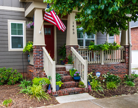 HICKORY, NC, USA-27 MAY 18:  A colorful house front, with green, blue, orange, and red.  A small American flag on either side of steps, and a larger one mounted higher on a porch column.