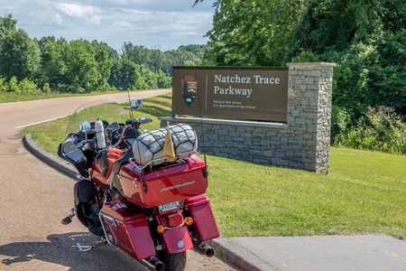 A motorcycle with camping gear strapped on, setting at the southern entrance to the Natchez Trace Parkway, in Mississippi, USA. Redakční