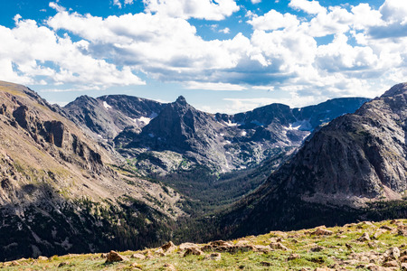 Sun shining on dramatic rocky mountains in Colorado, USA, bright green rock field in front, and bright white clouds in blue sky above. Good for background, text.