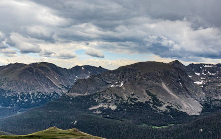 Clear, blue-gray Colorado Rocky Mountains, with dark evergreen forest in front, and two-pointed green rise in left-front.  Hint of storm clouds overhead.  Dramatic.  Good for background, text.