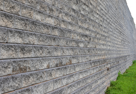 A concrete wall, built of  blocks creating horizontal rows, with a radiused setback for each row,.