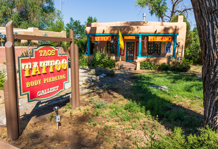 TAOS, NM, USA-7 JULY 18:  Taos Tattoo and Body Piercing Gallery is in a traditional pueblo structure on Paseo del Pueblo Norte, in downtown Taos. Publikacyjne