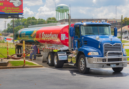 HICKORY, NC, USA-9618: A delivery man sits while fuel is pumped from his colorful Speedway truck. 報道画像