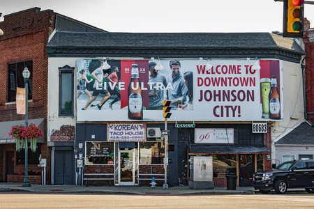 JOHNSON CITY, TN, USA-93018: A welcome sign sponsored by Michelob  is posted prominently in a square in downtown, with two small businesses below.