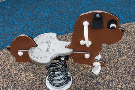 HICKORY, NC, USA-101418: A spring-mounted rocking dog, usually made as a rocking horse, in an outdoor playground.