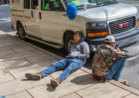 ASHEVILLE, NC, USA-101718: Two young male plumbers taking a break on the sidewalk.