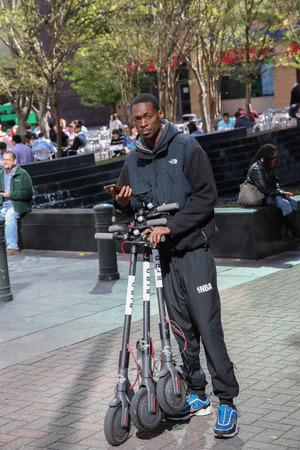 CHARLOTTE, NC, USA-103118:  A man collects electric scooters to re-stock locations in uptown. Editorial