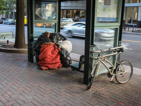 CHARLOTTE, NC, USA-103018:  An apparently homeless woman, with bags of possessions, sleeps at a bus stop on Tryon St. Editorial