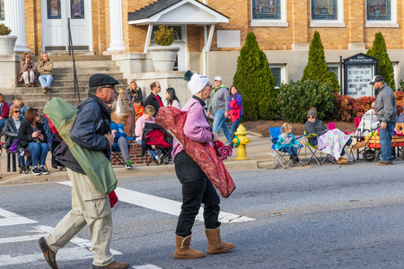 LINCOLNTON, NC, USA-112518: A senior couple carry bags with collapsible chairs before a local parade. Sajtókép