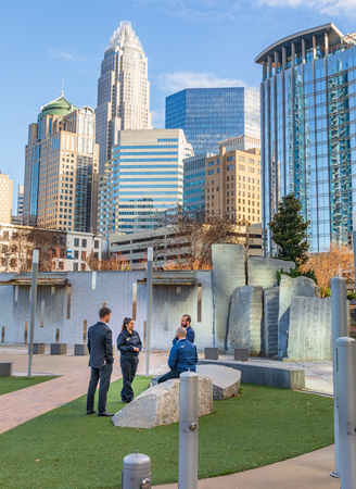 CHARLOTTE, NC, USA-1/8/19: Four people, 3 men and one woman, stand in grassy area of Bearden park and socialize.
