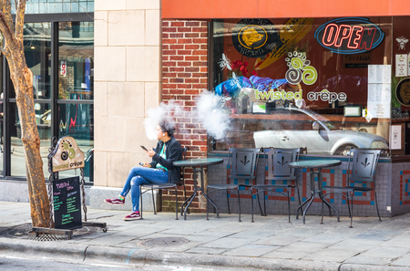ASHEVILLE, NC, USA-2/3/19: Young woman sitting in front of restaurant, using a vaping device, creating smoke.