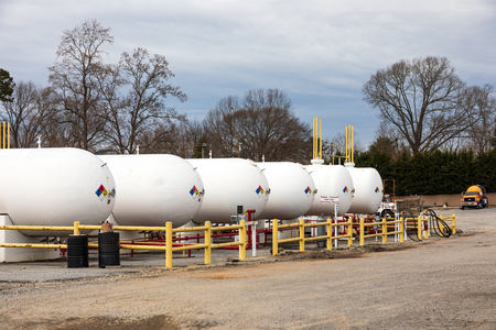 HICKORY, NC, USA-2/1/19: S line of large propane storage tanks and a propane delivery truck owned by James Oxygen. Editorial