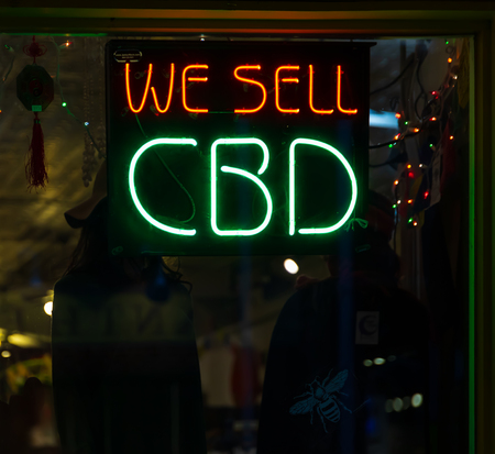 ASHEVILLE, NC, USA-21619: A store advertises cannabidiol with red and green neon signs.