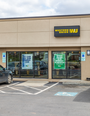 GASTONIA, NC, USA-31419: A Western Union Office, vertical view. People visible inside. 新聞圖片