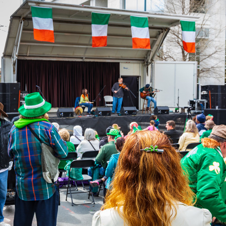 CHARLOTTE, NC, USA-31619: A red-haired woman stands and listens to an Irish music band on St. Patricks Day in uptown Charlotte.